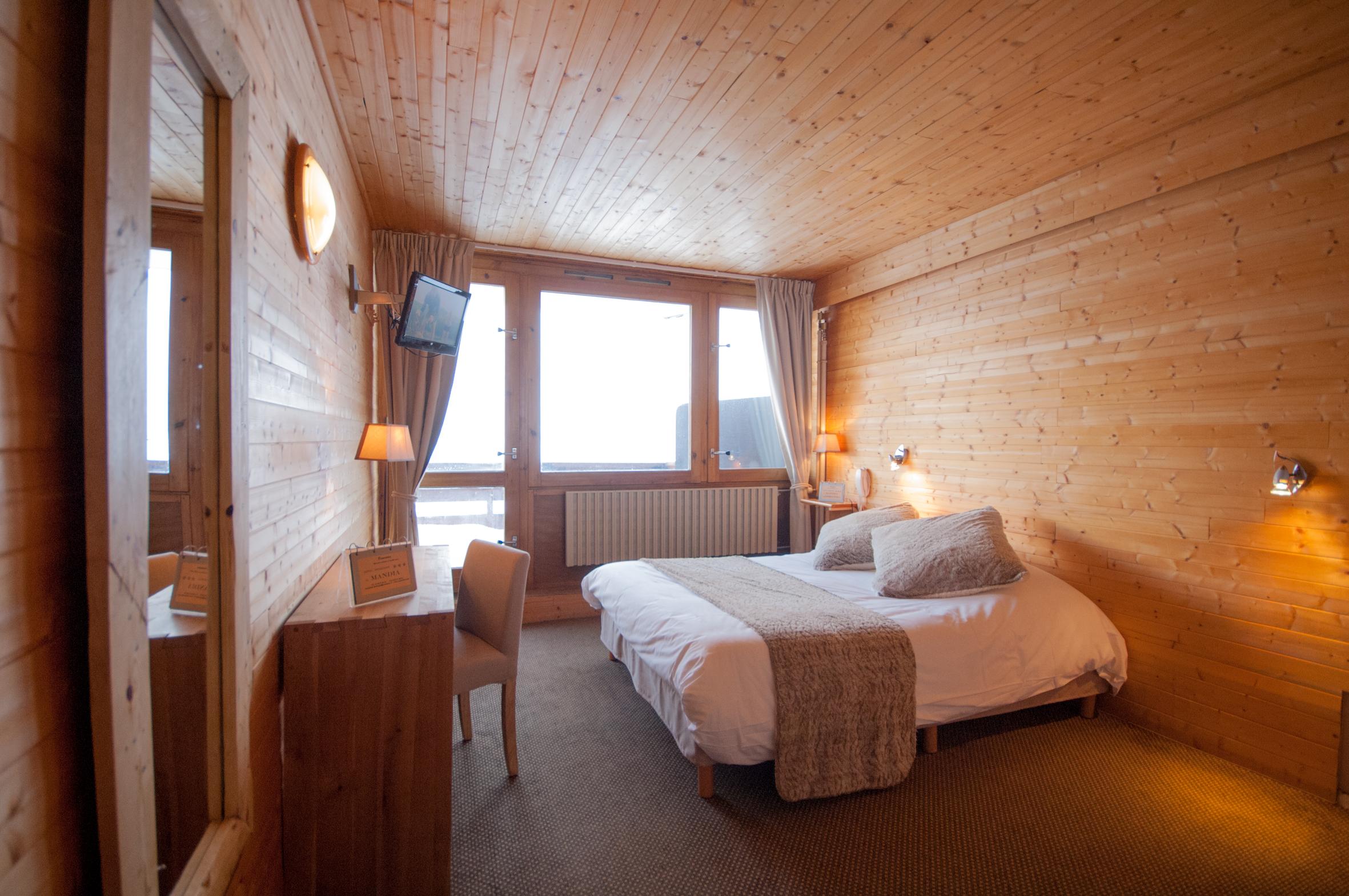 Photo d'une chambre bain de l'hôtel La Mandia, lit double, lit simple pour deux ou 3 personnes. Balcon avec vue sur les pistes de ski du Grand Tourmalet à La Mongie dans les Pyrénées.